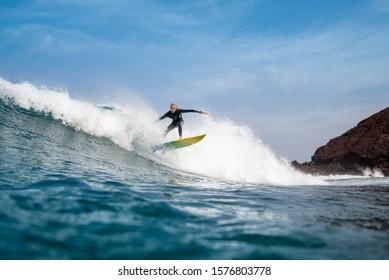 Fuerteventura - September 29, 2019: surfer riding waves on the island of fuerteventura in the Atlantic Ocean
