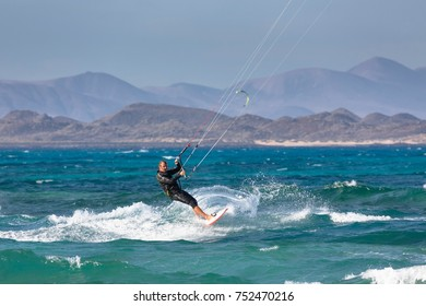 FUERTEVENTURA, SPAIN - CIRCA 2013: A middle aged man kite surfs off the coast of Corralejo in the Canary Island of Fuerteventura. Lanzarote is visible in the background beyond Isla de Lobos