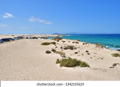 Fuerteventura, Spain - June 20, 2008: Car parking and scenic view of sand dunes on the beach Corralejo, Fuerteventura, Canary Islands