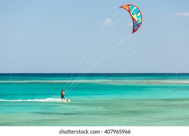 FUERTEVENTURA, SPAIN - SEPTEMBER 15, 2015: Unknown kitesurfer surfing on a flat azure water of Atlantic ocean in Corralejo, Fuerteventura, Canary islands, Spain