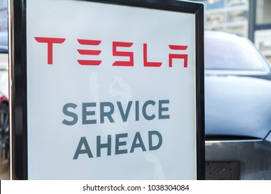 FUERTH / GERMANY - MARCH 4, 2018: Tesla service sign near a car dealer. Tesla, Inc. is an American company that specializes in electric automotives, energy storage and solar panel manufacturing.