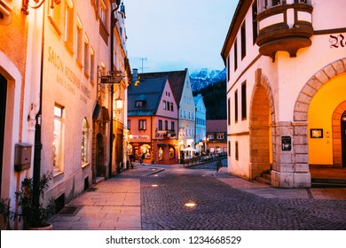 Fuessen, Germany - 28 March, 2018: Old Bavarian town near famous Neuschwanstein and Hohenschwangau Castles. Tourist attraction. Old town city centre at night.