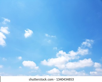 Fuffy clouds on bright blue sky background.