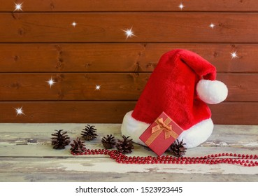 Fuffy Santa hat with pine cones and christmas gift on aged wooden table near wooden wall. View with copy space.