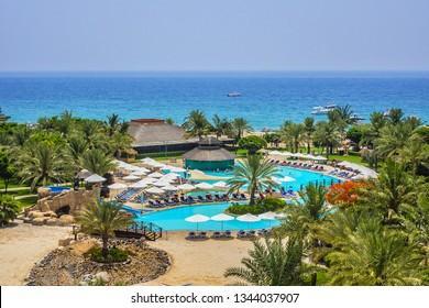 FUJAIRAH, UAE - JUNE 23, 2016: Five-star Fujairah Rotana Resort & Spa hotel (250 rooms and suites) in Fujairah located on shores of Indian Ocean near Hajar Mountains. Beautiful green hotel territory.