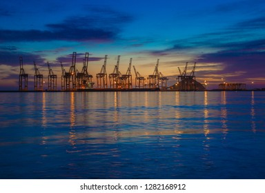 Fujairah / United Arab Emirates - 01/11/2019 : Early morning view of the Fujairah beach and its port, vivid blue sky and beautiful reflection in water.  Pictures taken before the sun rise