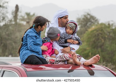 Fujeirah, United arab Emirates - circa February 2016: Emirati father with his kids sitting at the top of his car to watch bull fights