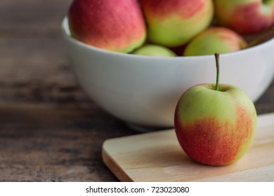 Fuji apple on cutting board put on rustic wood table and stack in white bowl with copy space.Delicious sweet and juicy suitable for salad cooking or bakery. Fuji apple has origins in Japan.