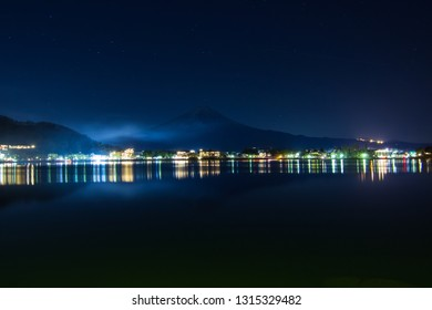 Fuji mountain during night time and the colorful light reflection in city of lake Kawaguchiko, Japan
