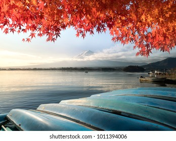 Fuji mountain and red leave maple tree at Kawaguchiko lake with a boat of fisherman , Japan .