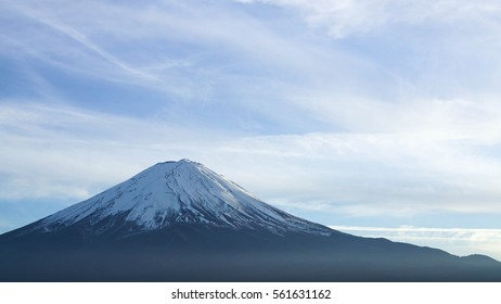 Fuji mountain with snow on the top in the Autumn season and white cloud blue sky with a little big of fog