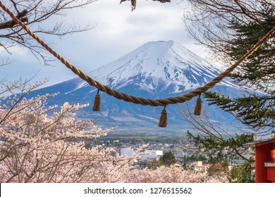 Fuji mountain from stair way at Chureito Red Pagoda Fujiyoshida,shimenawa enclosing rope leaning of cityscape view with pink full blooming sakura branches and clear sky in Japan.