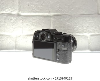 Fujifilm x-t30 with 18-55mm lens compact and black on a light brick wall background.