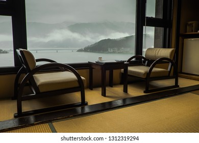 FUJIKAWAGUCHIKO, JAPAN - 10 APRIL 2017: Traditional room in a ryokan - Japanese hotel, with low chairs and table by the window. Misty mountains, lake and bridge are the view from the window.