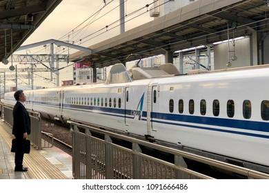Fukuoka, Japan - April 12,2018 - A Japanese salaryman standing and waiting for Shinkansen train to arrive at the platform