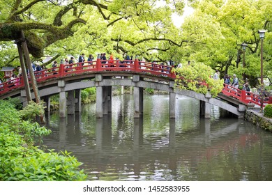 Fukuoka, Japan - April 30, 2019 : A crowd of tourists crossing the red wooden bridge at Dazaifu Tenmangu Shrine.