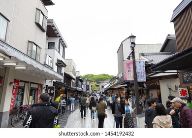 Fukuoka, Japan - April 30, 2019 : A crowd of tourists and shopping street with entrance stone torii gate at Dazaifu Tenmangu Shrine.