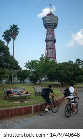 Fukuoka, Japan, August 3rd 2019 : A man resting on a park bench and two men cycling near Hakata Port Tower
