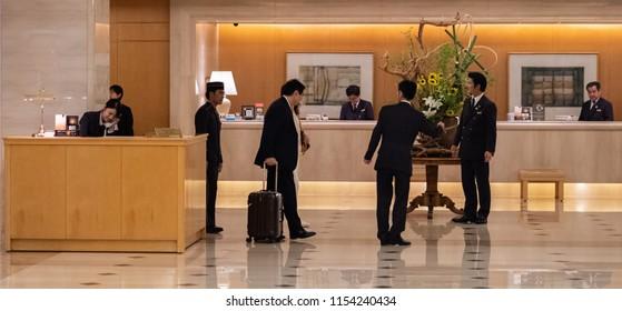 FUKUOKA, JAPAN - AUGUST 5TH, 2018. Guest arriving at Nikko Hotel reception desk.