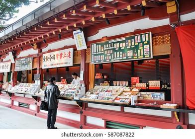 Fukuoka, Japan: December 16, 2009 -Unidentified man buying good luck charm at Dazaifu Tenmangu shop