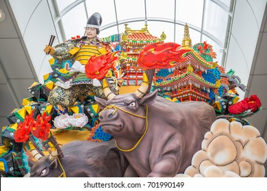 FUKUOKA, JAPAN - JULY 14, 2017: A  Shinto parade float, displayed on a sidewalk at the entrance to a shopping arcade during the Hakata Gion Yamakasa Festival, carries a samurai figure and giant bulls.