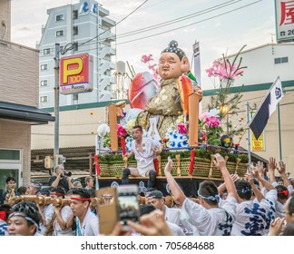 FUKUOKA, JAPAN - JULY 15, 2017: A team of men carries a heavy parade float of Ebisu, the god of luck, fishing, and the ocean, on their shoulders in a race during the  Hakata Gion Yamakasa Festival.