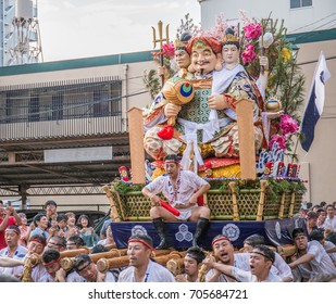 FUKUOKA, JAPAN - JULY 15, 2017: A team leader on a sacred Shinto parade float of Daikokuten, the god of wealth and proseprity, urges his team members forward in the Hakata Gion Yamakasa Festival.