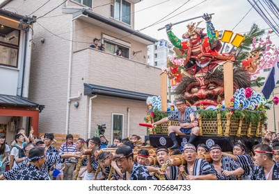 FUKUOKA, JAPAN - JULY 15, 2017: A team leader on a heavy parade float of a samurai on top of a demon, urges his team forward in the Hakata Gion Yamakasa Festival.