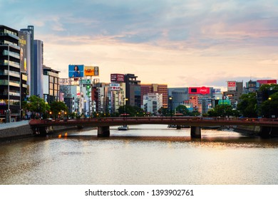 FUKUOKA, JAPAN - JULY 30, 2018: Car and people traffic during the morning in the center of Fukuoka, Japan. Modern buildings with different signs and billboards