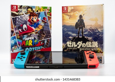 Fukuoka, Japan - june 6, 2019 :  Nintendo Switch with two hit games Super Mario Odyssey and zelda breath of the wild isolated on white background