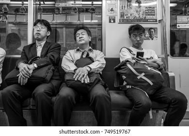 Fukuoka, Japan - May 19: Unidentified tired men in a tram on May 19, 2017 in Fukuoka, Japan