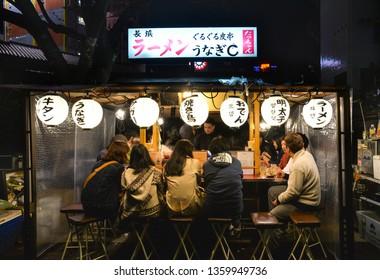 Fukuoka, Japan - November 16, 2018: People are having dinner at Yatai, local food stand, along the river near Canal city, Fukuoka, Japan
