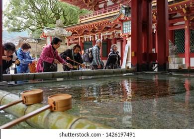 FUKUOKA, JAPAN - November 25, 2014 : Japanese people washing hands and mouth with Chozuya or Temizuya or Shinto water ablution pavilion Dazaifu shrine, Fukuoka, Japan.