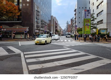 Fukuoka, Japan - November 26, 2014 : Cars and people passing zebra crossing with modern city background. pedestrian crossing on traffic road.