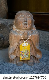 Fukuoka, Japan - October 20, 2018: Old stone buddha statue with a Japanese amulet called omamori at the Shofukuji temple grounds