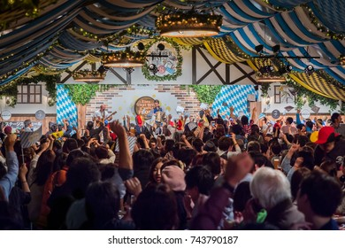 FUKUOKA, JAPAN - OCTOBER 21, 2017: A large crowd cheers on a German band during Kyushu's largest annual Oktoberfest, featuring traditional beer, food, and music for 9 days each October in Reisen Park.
