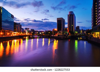Fukuoka, Japan. A sunrise in central Fukuoka, Japan, with a view of the Naka river, illuminated prominent skyscrapers and a clody colorful sky.