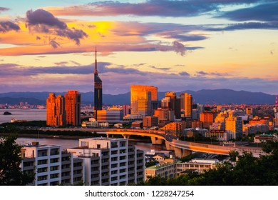 Fukuoka, Japan. A sunset with a view of central Fukuoka, Japan, with tall modern buildings standing by the Hakata Bay on a cloudy summer evening.