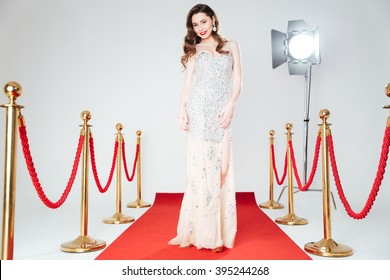 Ful llength portrait of a charming woman walking on red carpet