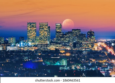 Ful moon rising over Los Angeles skyline at dusk. View of Century City and Pacific Ocean.