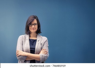 Fulfilled businesswoman and female leader. Portrait of confident female entrepreneur with arms crossed looking at camera. Copy space.