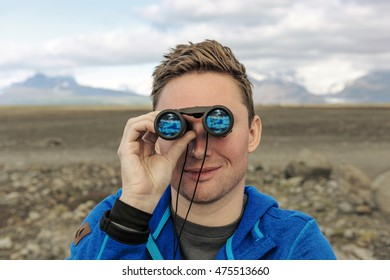 Full of adventure. Man looking through binoculars at mountains landscape in Iceland.