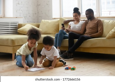 Full African family gathered in modern living room, while parents resting on couch using cell little kids drawing on paper using pencils enjoy playtime on warm wooden floor with underfloor heat system