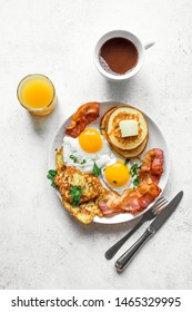 Full American Breakfast on white, top view, copy space. Sunny side fried eggs, roasted bacon, hash brown, pancakes, orange juice and coffee for breakfast.