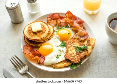 Full American Breakfast on white table, close up. Sunny side fried eggs, roasted bacon, hash brown, pancakes, orange juice and coffee for breakfast.