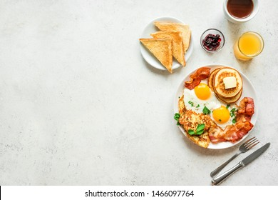 Photo of Full American Breakfast on white, top view, copy space. Sunny side fried eggs, roasted bacon, hash brown, pancakes, toasts, orange juice and coffee for breakfast.