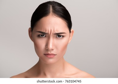 Full of anger. Close-up portrait of young naked asian girl is standing and looking at camera with annoyance while frowning her forehead. Isolated background