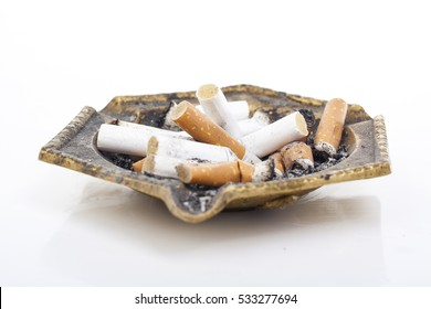 Full ashtray can illustrate your work. Copper cigarette ashtray. Dirty ashtray in white studio background. Tobacco cigarette butts in ashtray.