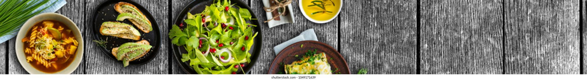 Full banner, wide food background, vegetarian meal and healthy products on rustic wooden table, wide panoramic image. Copy space. Top view.