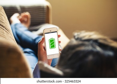 Full battery concept. Woman lying on a sofa, holding mobile phone with full battery green icon in the screen.